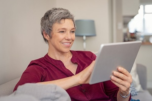 A happy mature woman sitting in a lounge using a tablet device